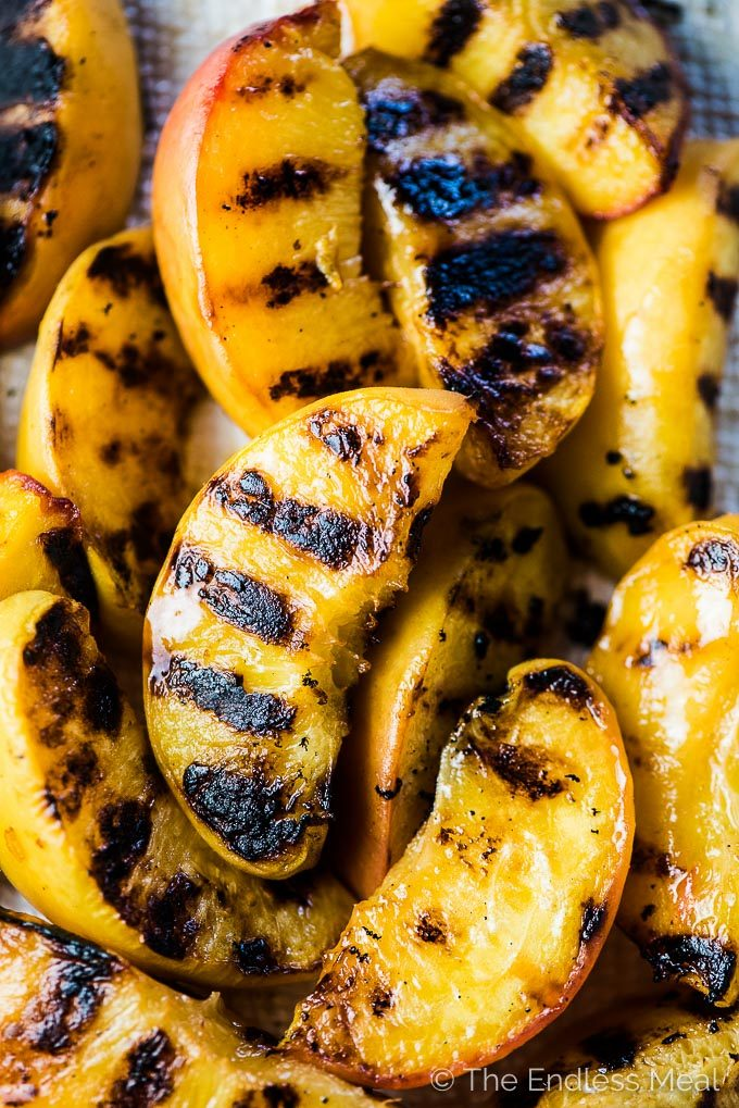 A close up shot of grilled peaches on a white plate ready to go into the grilled peach salad.
