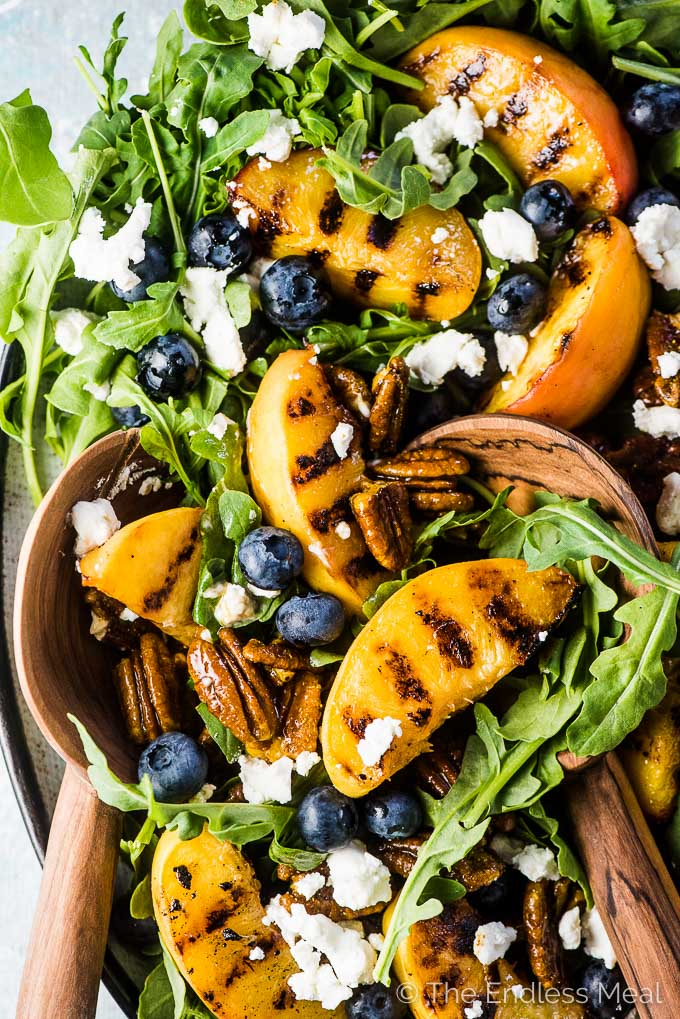 A grilled peach salad with blueberries and arugula on a large platter with wooden salad tongs.