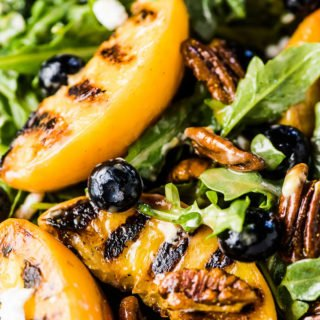 A close up shot of the grilled peach salad tossed in a honey vinaigrette with arugula, blueberries, goat cheese, and candied curry pecans.