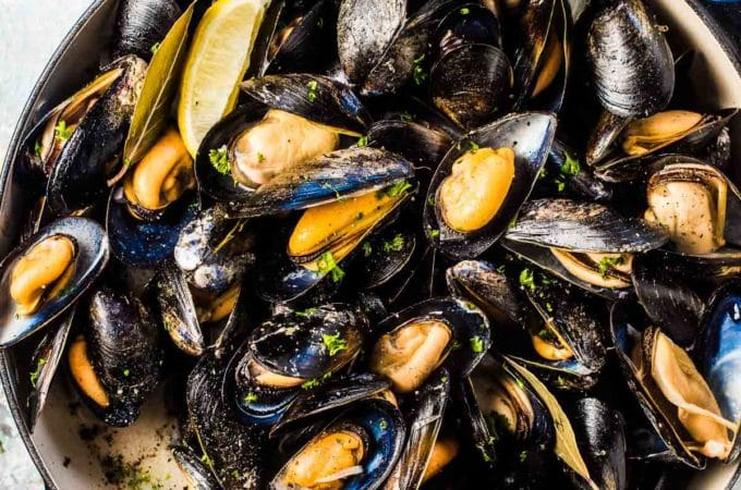 After learning how to make mussels, they are sitting in a big pot of mussels in white wine on a blue and white table.