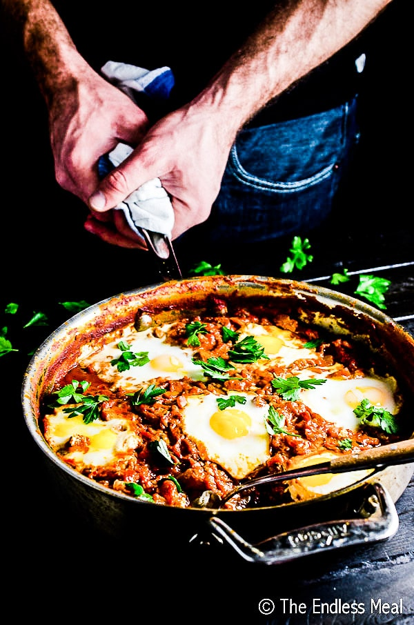 A man's hands holding a pot of harissa shakshuka.