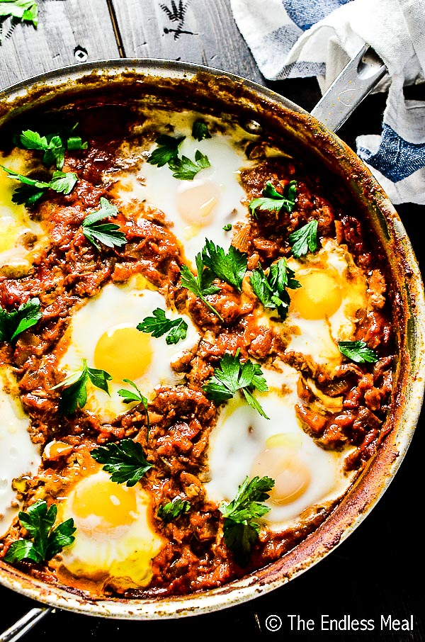 A close up of harissa shakshuka in a pan.