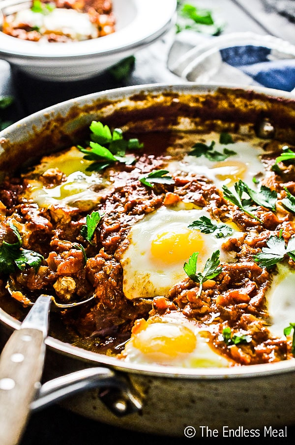 A pan of harissa shakshuka with a serving spoon in it.