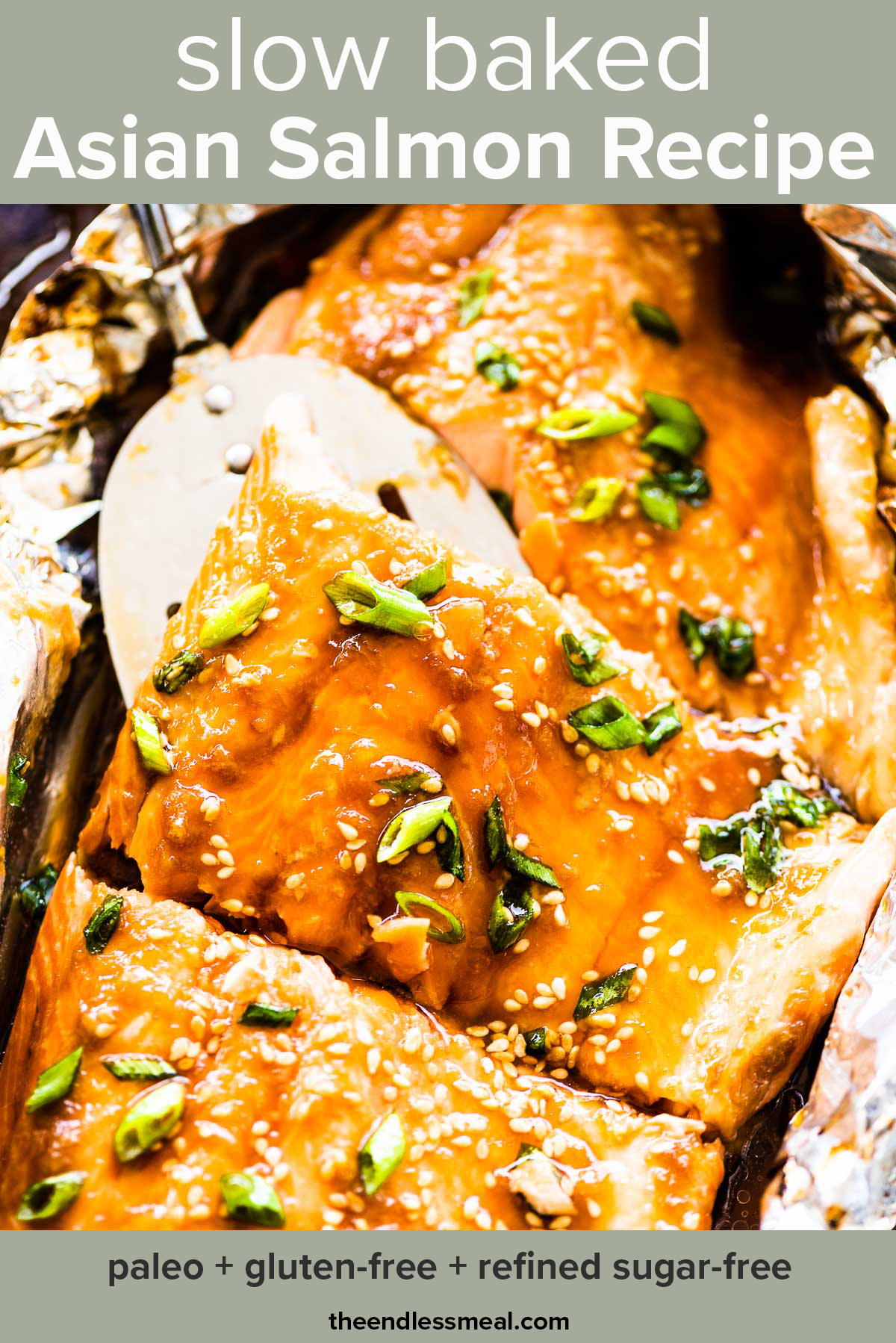 Glazed Asian salmon in foil on a baking sheet with a spatula lifting a piece of salmon and the recipe title on top of the picture.