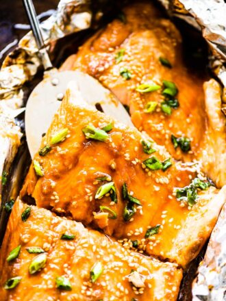 Glazed Asian salmon in foil on a baking sheet with a spatula lifting a piece of salmon.