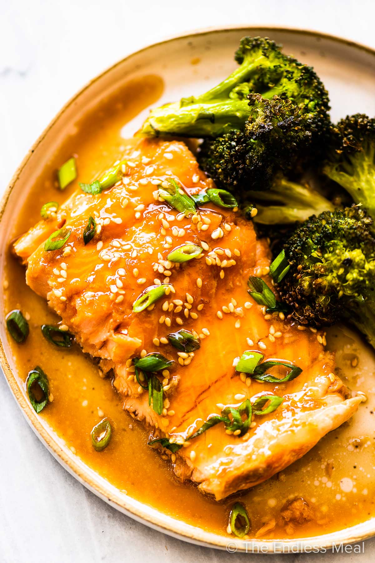 Glazed Asian salmon in a dinner plate with broccoli on the side/
