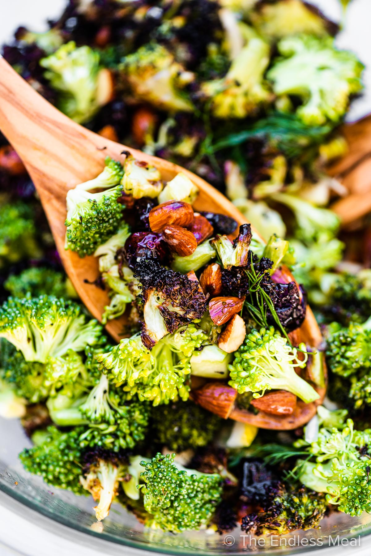 A scoop of roasted broccoli salad on a wooden spoon.