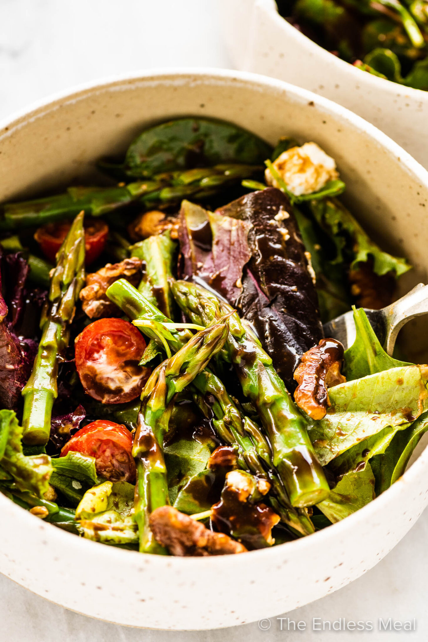 Asparagus salad in a bowl with a fork.