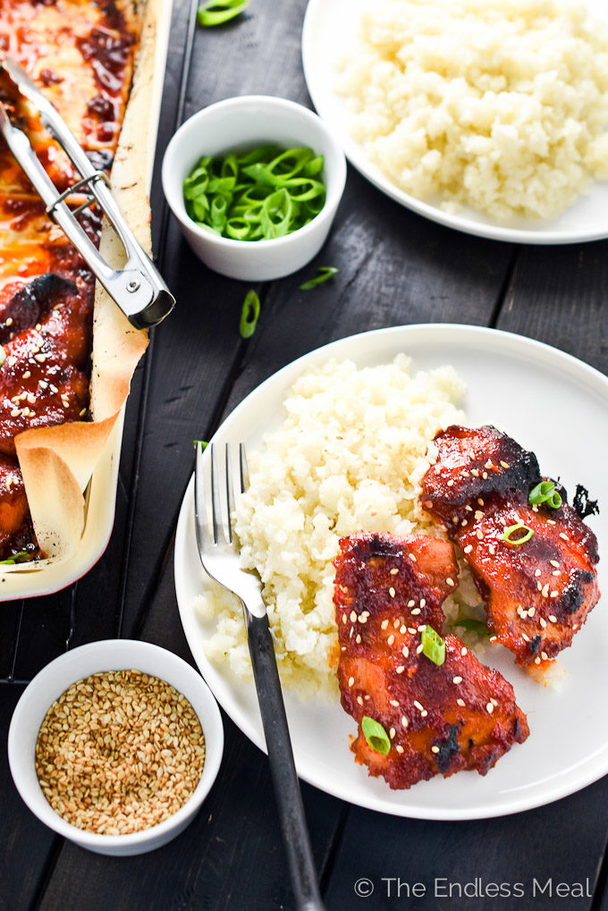 Sweet Korean Paleo Chicken Thighs with Cauliflower Rice on a plate on a black table.