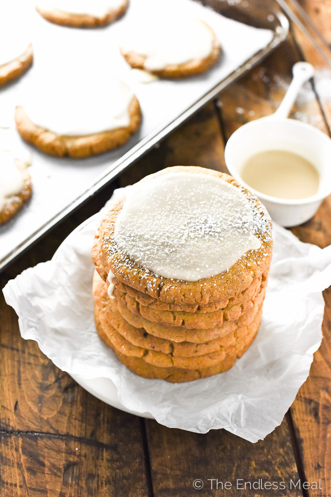 Pumpkin sugar cookies stacked on a plate.