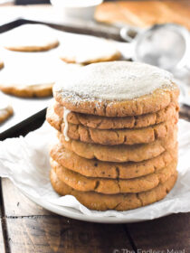 A stack of crispy pumpkin sugar cookies on a plate.