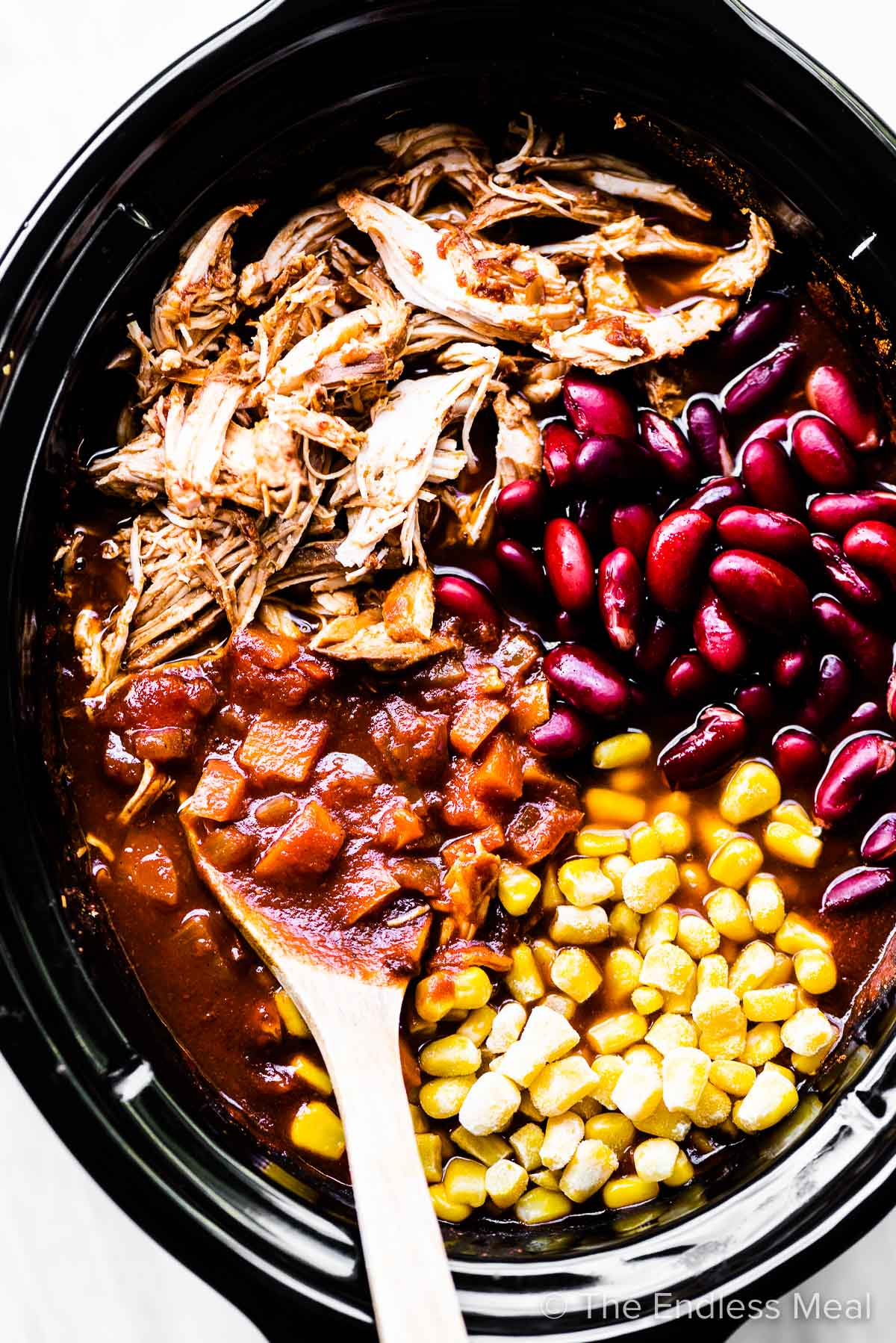 All the ingredients for this chicken chili in a slow cooker.