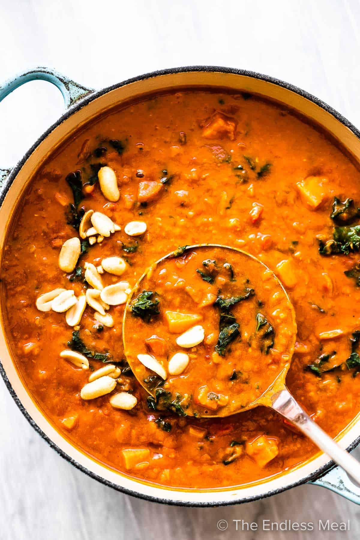Coconut Red Lentil Peanut Soup in a soup pot with a ladle.