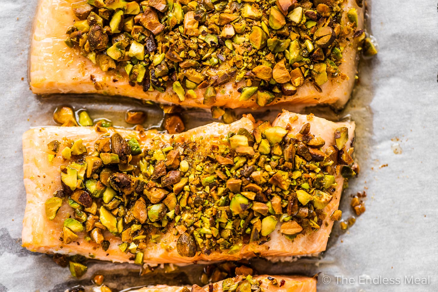 Pistachio crusted salmon on a baking sheet.