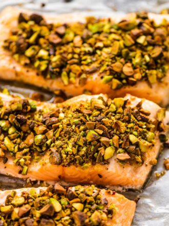 A close up of pistachio crusted salmon on a baking tray.