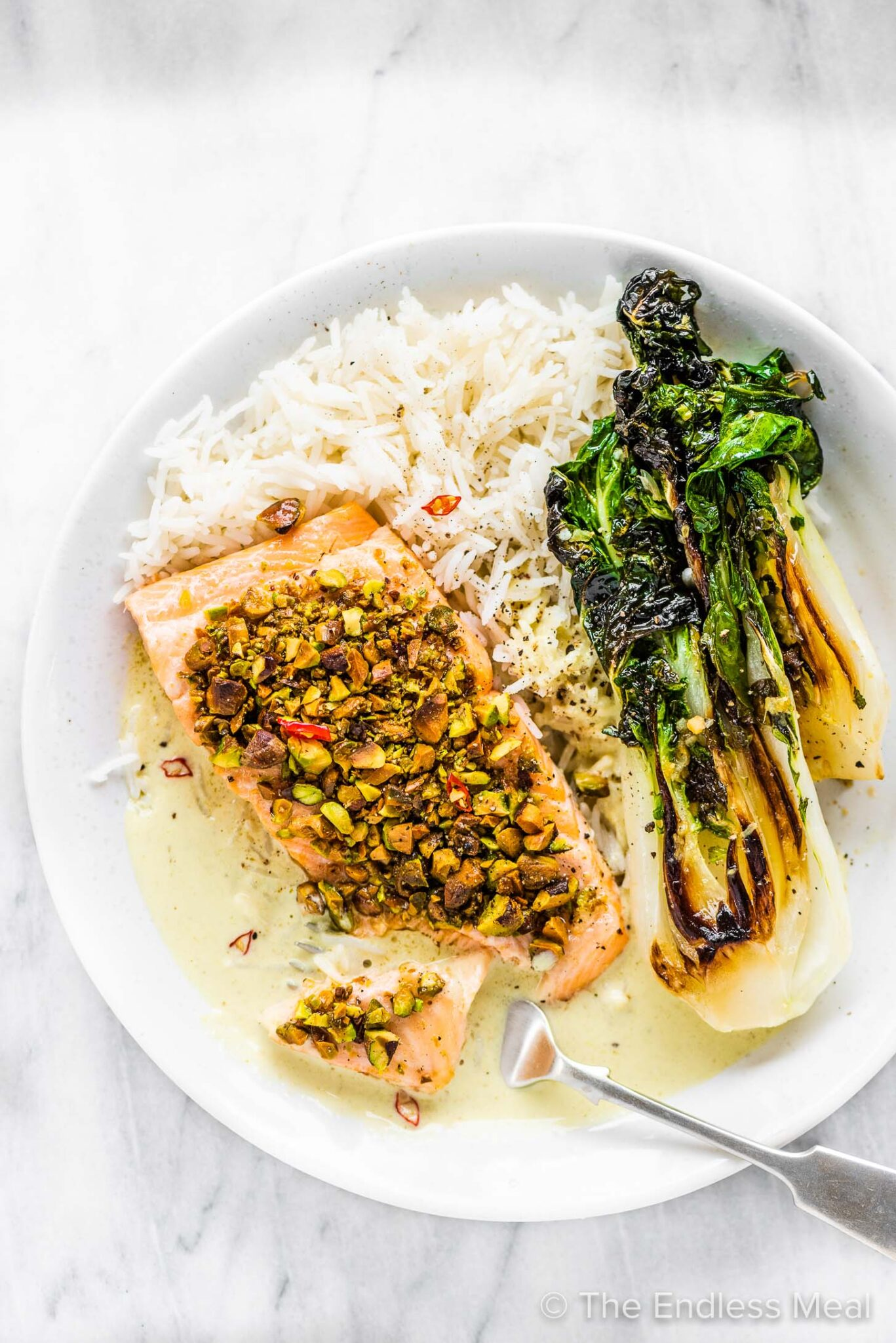 Pistachio salmon on a white plate with rice and bok choy.