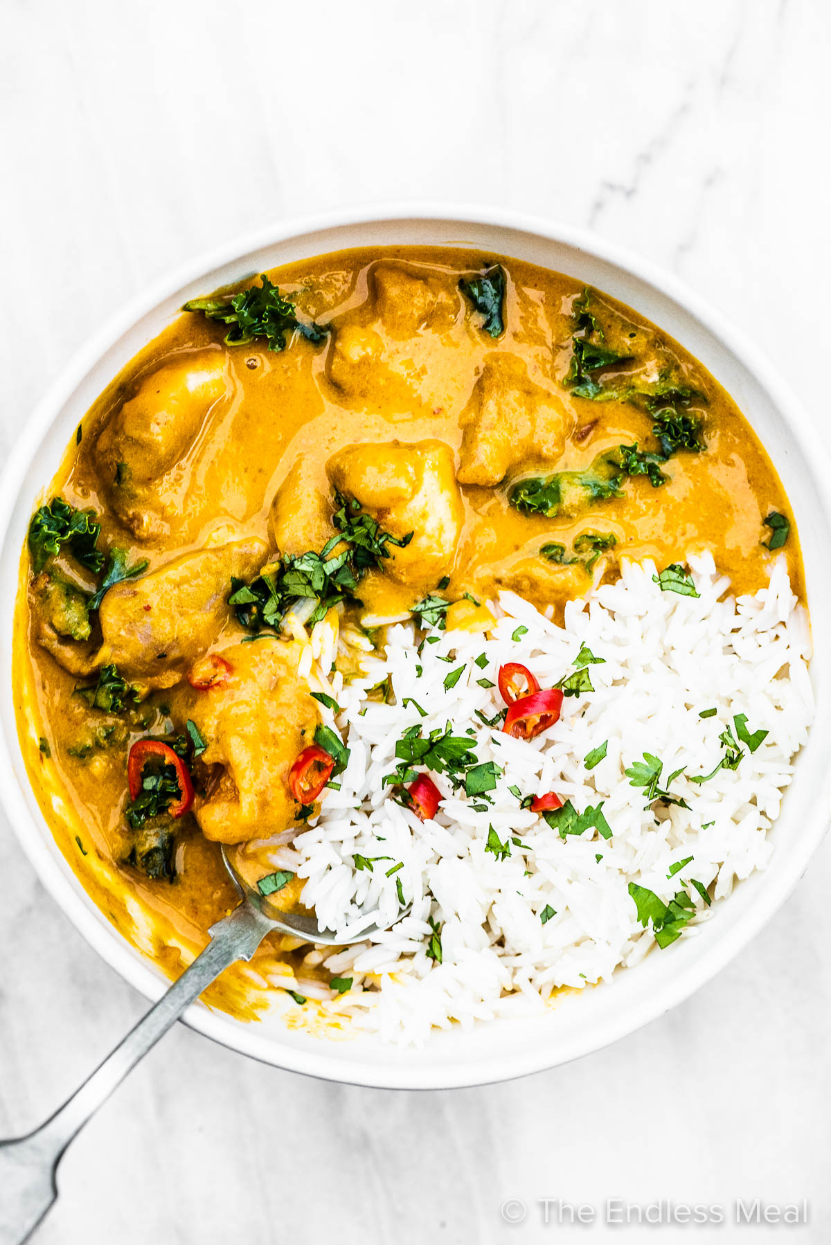A bowl of rice and Thai chicken curry with a spoon inside.