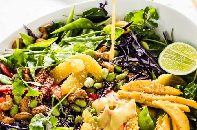 Sweet mango sesame dressing being poured over the chopped Thai salad.