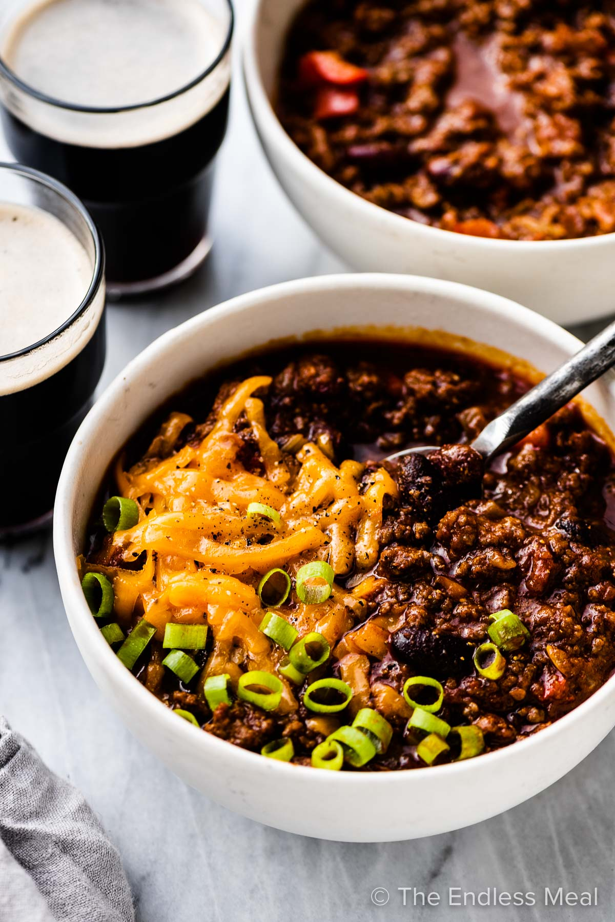 Two bowls of Irish chili with glasses of Guinness on the side.