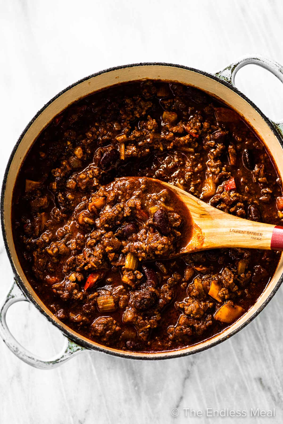 A white pot filled with Guinness spiked Irish chili and a wooden spoon taking a scoop.