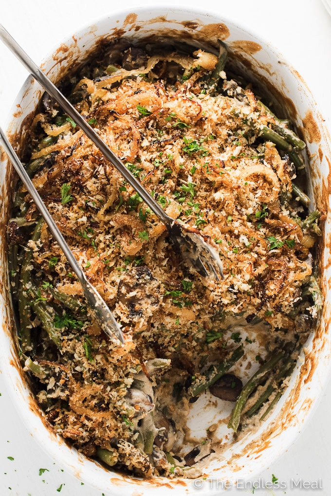 Healthy Vegan Green Bean Casserole with a scoop taken out and serving tongs on top.