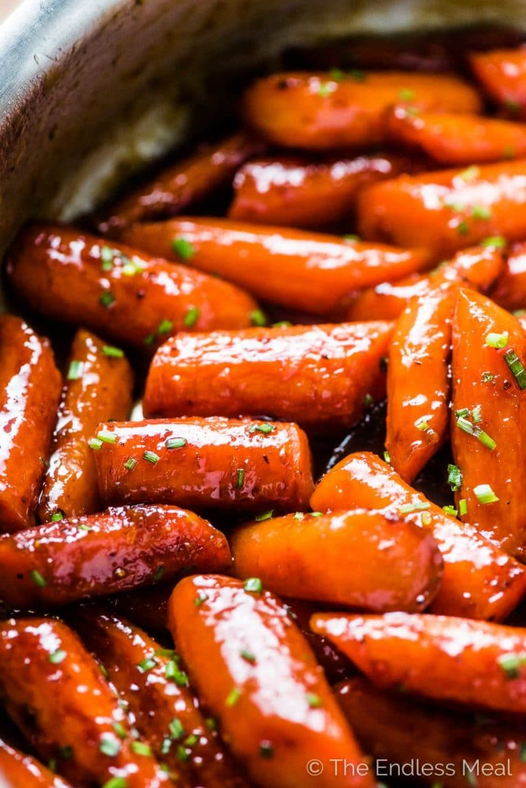Sticky honey roasted carrots in a pan.