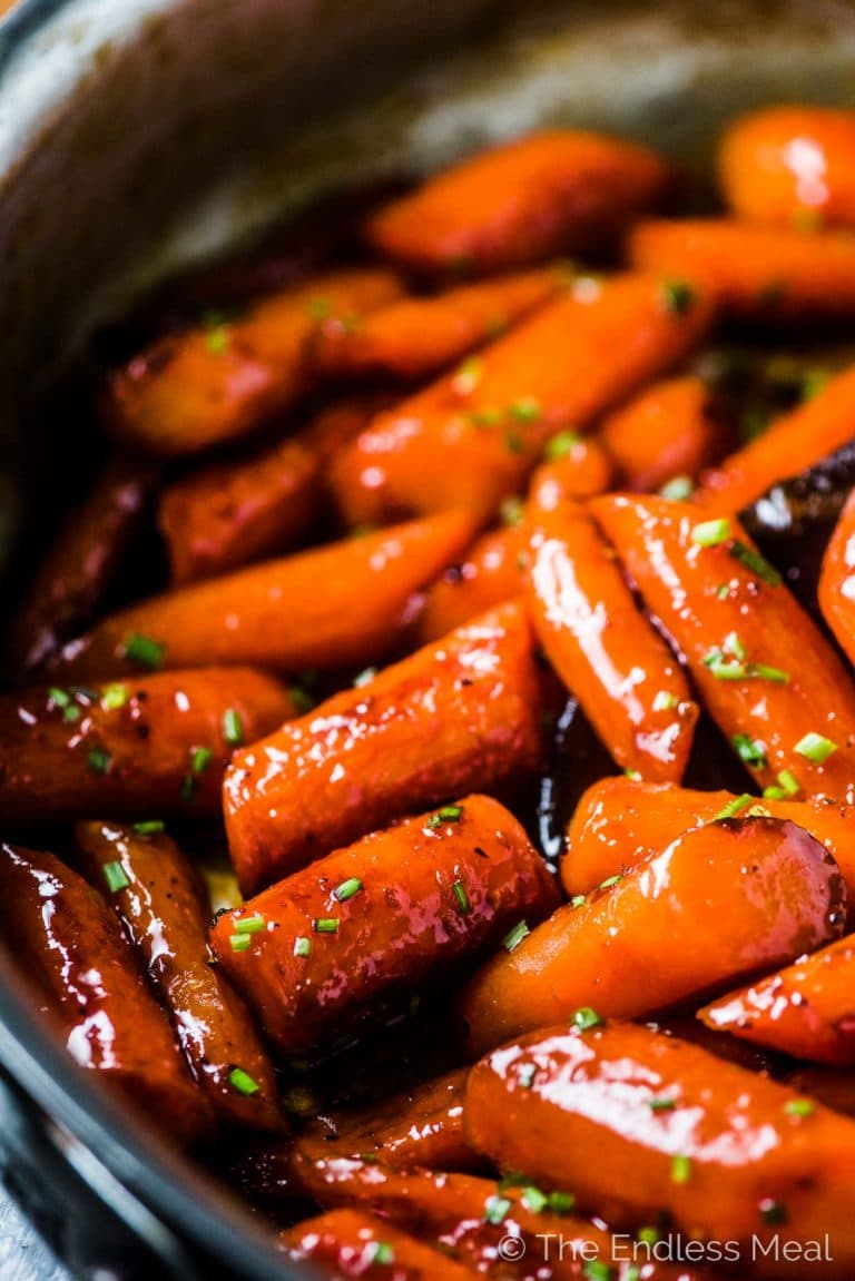 A close up of honey glazed carrots in a skillet.