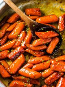 A skillet full of glazed honey roasted carrots (candied carrots!) with some minced chives sprinkled over the top.