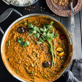 A pot filled with creamy coconut lentil curry with some cilantro on the top.