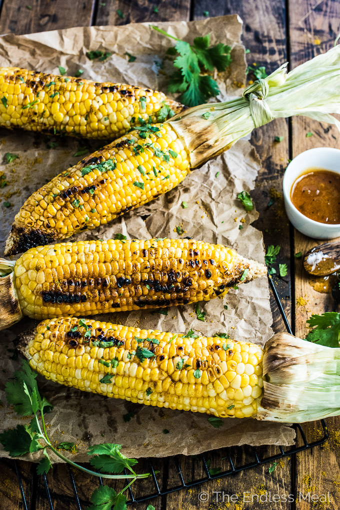 Curry corn on the cob is basted in mango chutney butter and sprinkled with curry powder then grilled to sweet perfection. It makes an addictive side dish to any summer BBQ or picnic. You will LOVE it! | theendlessmeal.com