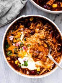 A spoon in a white bowl filled with crockpot chicken chili.