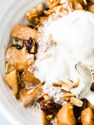 Vanilla ice cream melting over this healthy apple crisp recipe and a spoon taking a bite.
