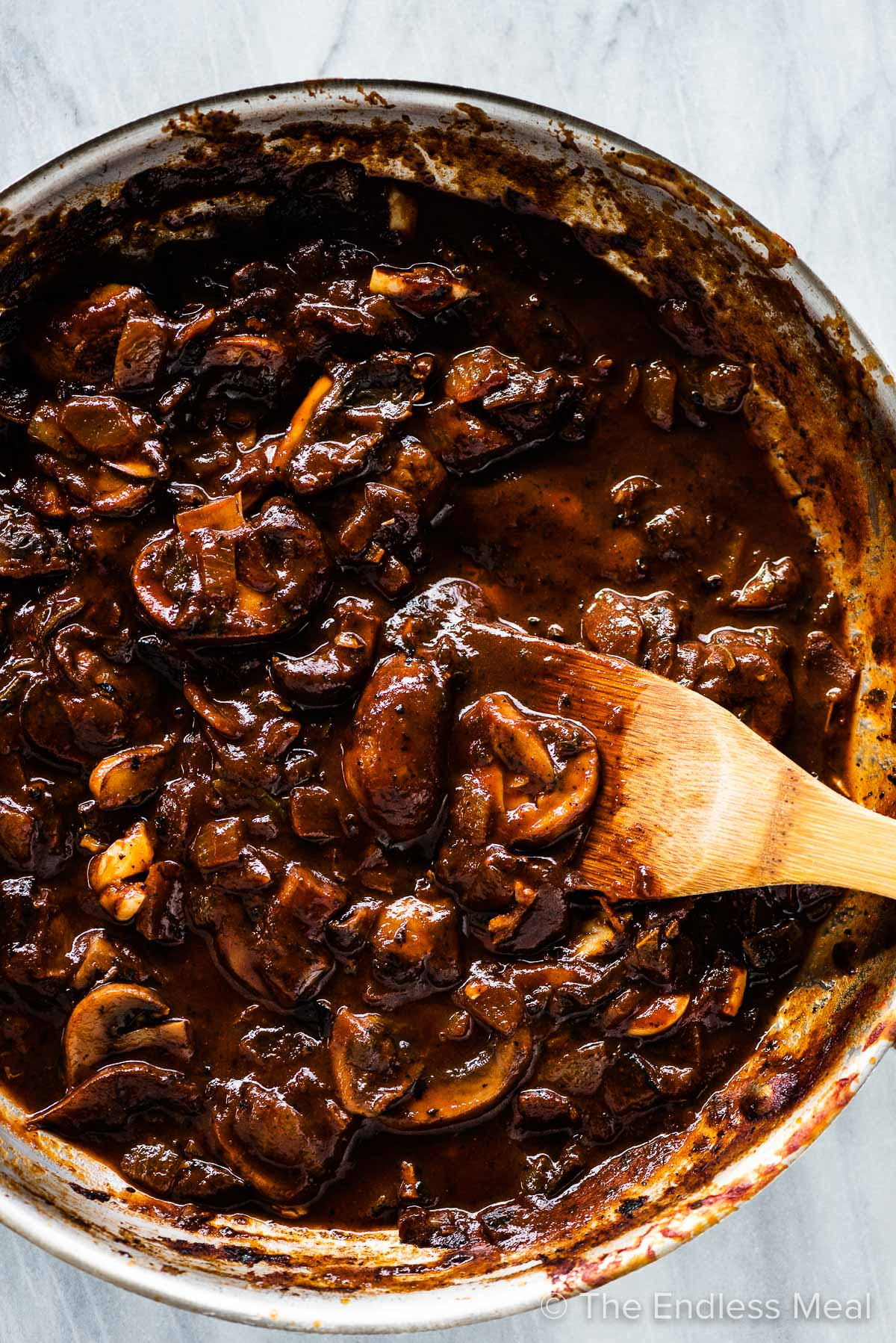The cooked mushrooms and other ingredients in a pan before the gravy goes into the blender.
