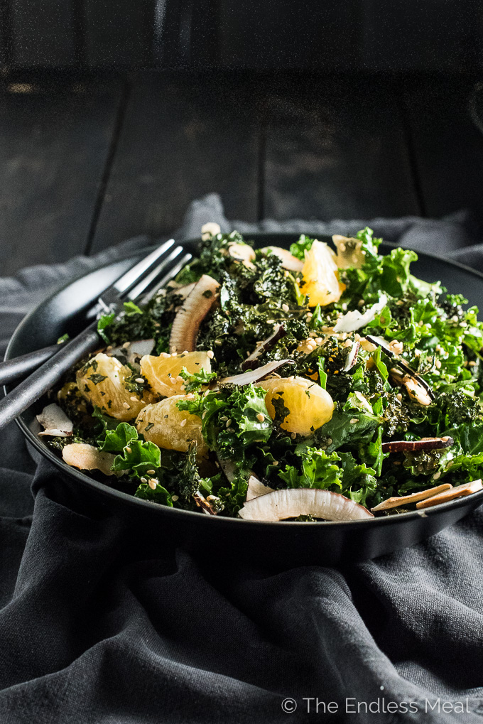 This Sesame Coconut Kale Salad has become our go to winter salad recipe. It's made with crispy kale AND raw kale and dotted with sesame, toasted coconut, and mandarines. The dressing is light and crisp with hints of Asian sesame oil. | theendlessmeal.com