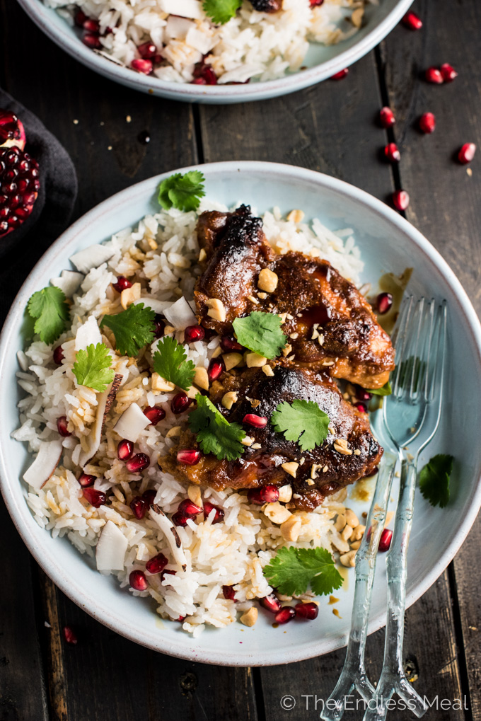 Thai Peanut Pomegranate Chicken layered on top of white rice in a bowl for one of the best gluten free chicken dinners.