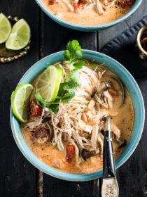 A blue bowl filled with crockpot Thai chicken soup with a spoon it it on a black wooden table.