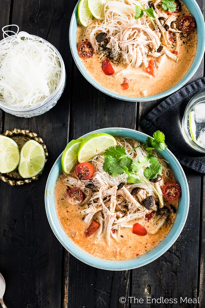Two blue bowls filled with crockpot Thai chicken soup on a black wooden table with limes and a bowl of rice vermicelli and a glass of water on the side.