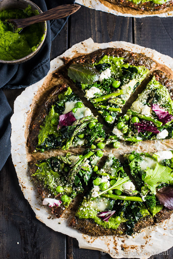 This pretty Green Goddess Pizza is made with a green veggie pizza crust, pesto pizza sauce, and piled lightly with kale, asparagus, peas, and hemp hearts. It's an easy and delicious way to eat your greens at dinner. | theendlessmeal.com