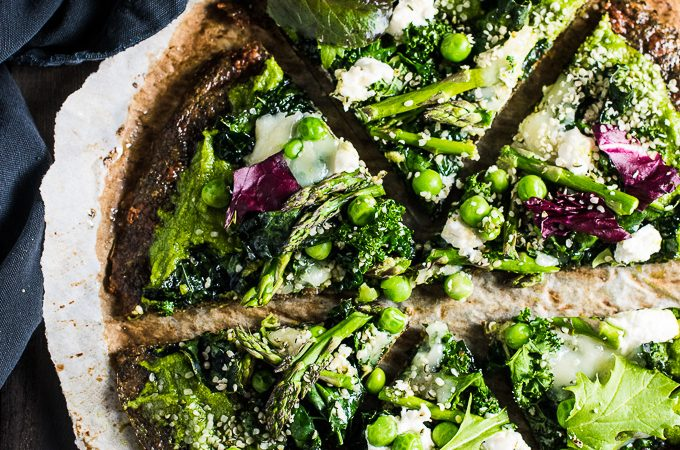 This pretty Green Goddess Pizza is made with a green veggie pizza crust, pesto pizza sauce, and piled lightly with kale, asparagus, peas, and hemp hearts. It's an easy and delicious way to eat your greens at dinner.   theendlessmeal.com