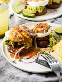 These Mexican-style Sweet Potato Eggs Benedict start with roasted sweet potatoes rounds that are topped with roasted tomato, chunky guacamole, and poached eggs then smothered in chipotle hollandaise. They're an insanely delicious breakfast recipe that just happens to be vegetarian + gluten-free +paleo + Whole30 approved. | theendlessmeal.com