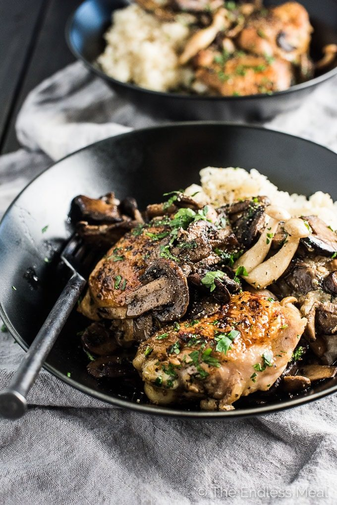 This crispy skinned, Pan Fried Chicken and Mushrooms is the ultimate feel-good comfort food. The chicken is seared in a skillet with loads of mushrooms then served over an easy to make cauliflower mash. It's a healthy dinner recipe that is so delicious. It's also naturally dairy free + paleo + low carb + Whole30 compliant.   theendlessmeal.com