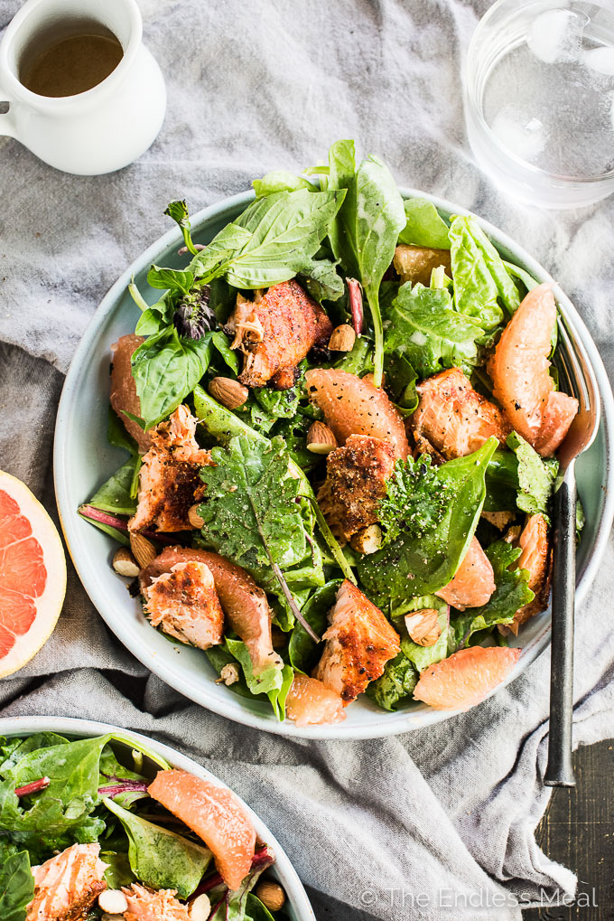 This fresh and tropical Grilled Salmon Salad is as delicious as it gets. Toss your favorite spring greens in a grapefruit coconut salad dressing and top with bites of grapefruit, chopped almonds, a little dill, and spicy grilled salmon. It's a healthy lunch or dinner recipe that is gluten-free + paleo + Whole30 approved. | theendlessmeal.com