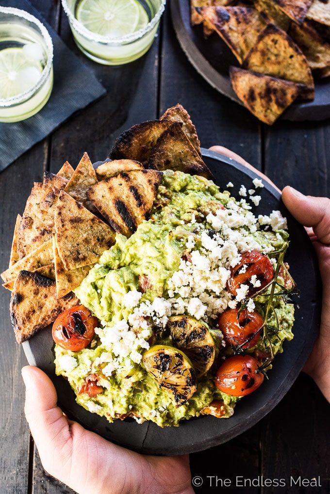 Hands holding a big bowl of chunky grilled guacamole over a black table makes the ideal summer side dishes.