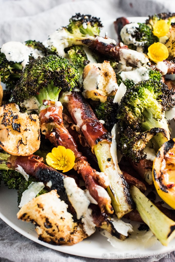 This insanely delicious Grilled Broccoli Caesar Salad is fun and summery take on our fav salad recipe. The broccoli is wrapped in salty prosciutto that turns crispy when grilled. The dressing is an easy to make and lightened up (read: healthy!) version made with yogurt. You will LOVE this! | theendlessmeal.com