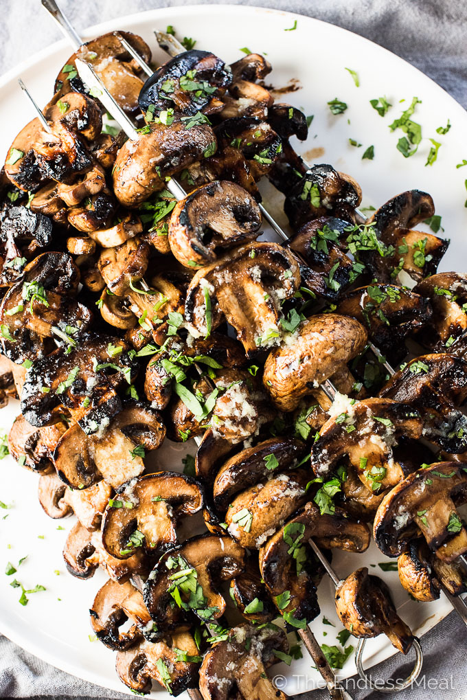 Grilled Garlic Butter Mushrooms on skewers on a white plate.