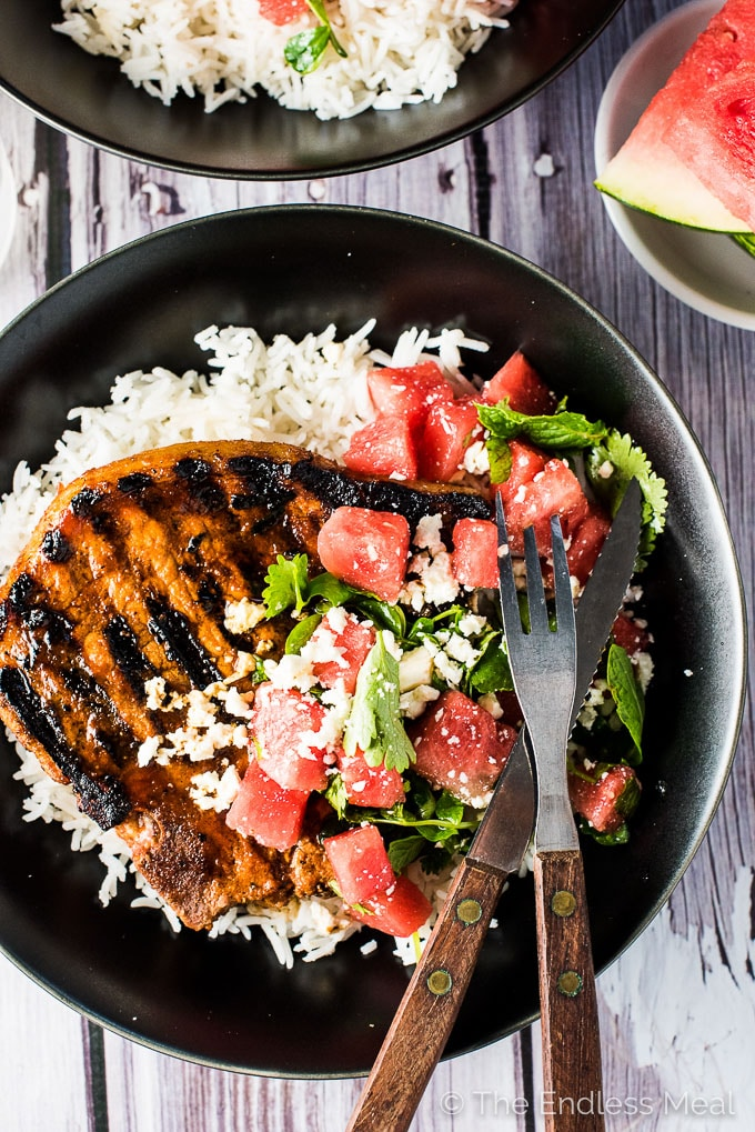 Grilled Gochujang Pork Chops are a delicious and healthy summer BBQ recipe.They are marinated in a sweet and spicy Korean chili paste then grilled to perfection. Serve them with a side of rice (or cauliflower rice!) and a simple mint watermelon salad for an easy and healthy dinner recipe.  theendlessmeal.com