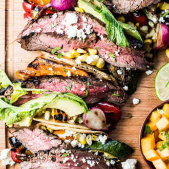 Steak tacos on a cutting board filled with lots of summer veggies.