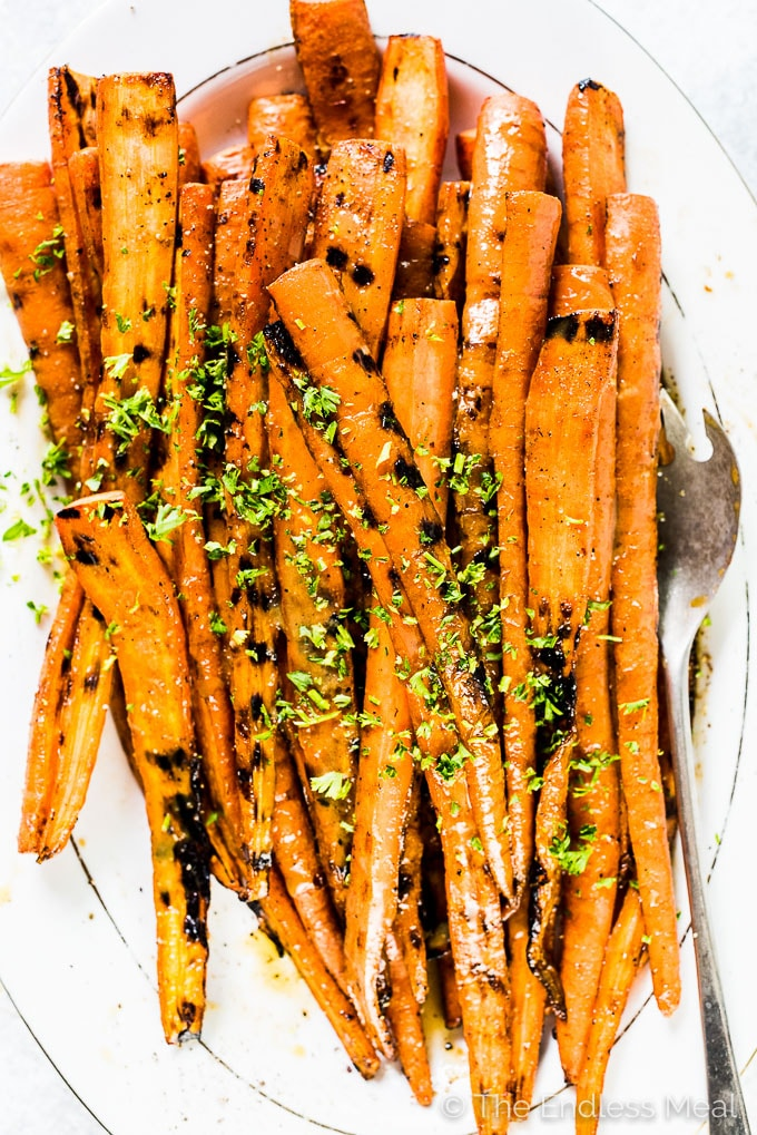 These might just be the best darn Maple Dijon Carrots ever. No lie. They're grilled on the BBQ then covered in an easy to make and super delicious maple dijon sauce. They're a naturally vegan + gluten-free + paleo side dish recipe that everyone will fall in love with.  | theendlessmeal.com