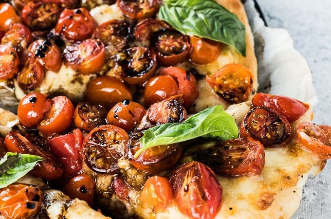 Hello, summertime pizza! This delicious Easy Caprese Pizza is loaded with sweet cherry tomatoes and fresh mozzarella then topped with basil and reduced balsamic once it comes out of the oven. It's an easy and healthy way to eat pizza all summer long.  | theendlessmeal.com