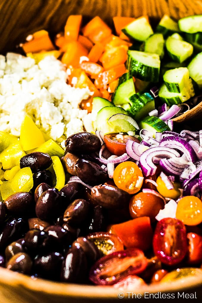 A close up of the ingredients for this Greek salad recipe in a wooden bowl.
